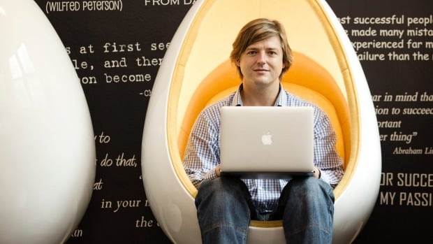 Danny Adams, Founder of GOFAR seated on a pod chair with laptop.