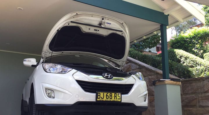 White hyundai car with bonnet open for servicing