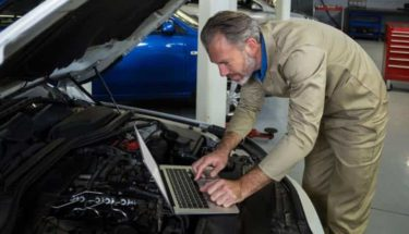 A mechanic fixing a check engine light warning. Using a laptop to daigonise.