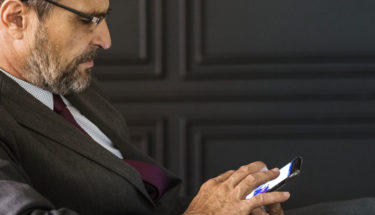 Man wearing a corporate attire using mobile device