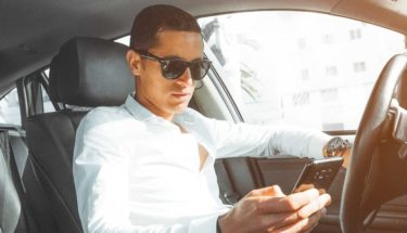 man checking his mobile phone inside the car