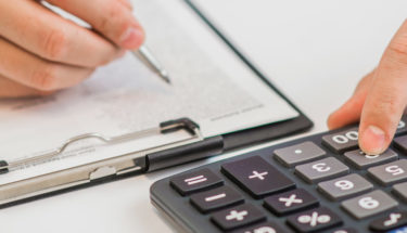 close-up businessman calculating expenses