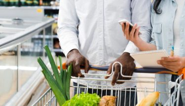 couple with shopping cart checking on mobile shopping list at supermarket